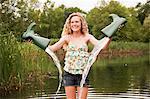 Teenage girl emptying wellies beside lake