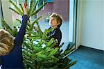 Boys decorating Christmas tree at home