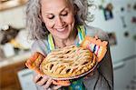 Senior woman holding freshly baked pie