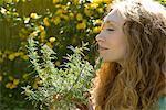 Woman smelling herbs in backyard