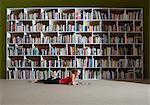 Girl reading by bookshelves