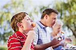 Boy eating melon at picnic table