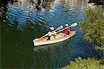 Older couple rowing canoe on lake