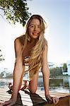 Woman in bikini crawling on deck