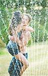 Friends hugging in sprinkler