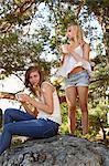 Teenage girls having coffee in forest