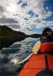 Woman rowing kayak in still lake