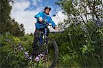 Man mountain biking on dirt path