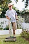 Older man mowing lawn in backyard