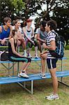 Friends talking on bleachers in park