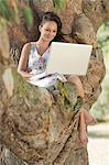 Smiling woman using laptop in tree