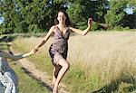 Teenage girls skipping on dirt path