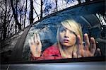 Woman peering out car window in woods