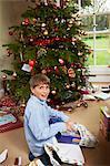 Smiling boy opening Christmas gift