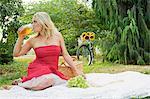 Woman drinking from jar at picnic