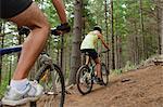 Couple mountain biking in forest