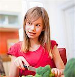 Girl slicing vegetables in kitchen