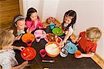 Children dipping vegetables in sauce