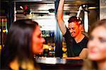 Bartender waving to customers in bar