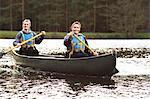 Women rowing canoe on still lake