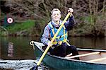 Woman rowing canoe on still lake