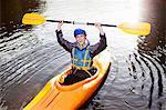 Kayaker holding oar in still lake