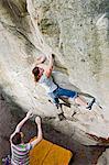 Climber spotting woman on steep cliff