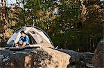 Hiker sitting on camp pad on boulder