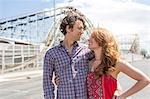 Romantic couple gazing at each other at amusement park