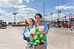 Portrait of couple with inflatable monkeys at amusement park