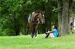Horse rider sitting beside tree, horse beside