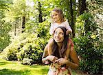 Mother giving toddler daughter a shoulder carry in park
