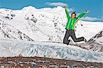 Mature female hiker jumping mid air in mountains, Svinafellsjokull, Vatnajokull National Park, Iceland