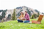 Romantic mid adult couple having champagne picnic, Wallberg, Tegernsee, Bavaria, Germany