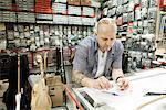 Guitar maker measuring up blueprint design in workshop