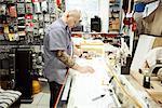 Guitar maker measuring up blueprint design on drawing table