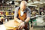 Guitar maker measuring wooden guitar shape in workshop
