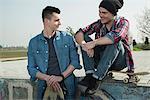 Young men sitting together at skatepark