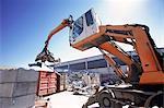 Grapple handler sorting and moving metals in scrap yard