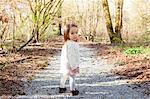 Baby girl walking on gravel path