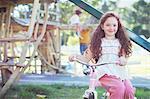 Smiling girl sitting on bicycle at playground