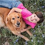 A young girl hugging a golden retriever pet.