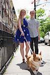 Young couple taking corgi dog for a walk along street