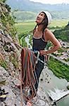 Female climber at belay point on multi pitch route, Amazziona at Piccolo Dain Parete della Centrale, Sarche, Trentino, Italy