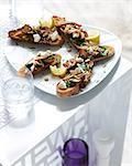 Plate of mushroom and spinach bruschetta with lemon slice