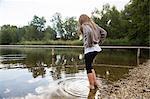 Girl paddling and looking down at lake