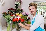 Portrait of mid adult man arranging flowers in vase, smiling