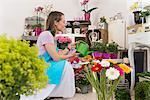Mid adult woman watering flowers in shop