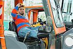 Construction worker sitting in excavator