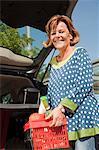 Senior woman stowing basket in car trunk